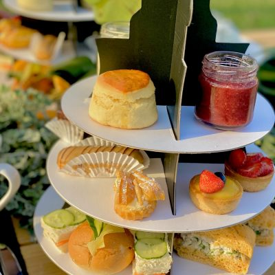 An Afternoon Tea to remember. A 3-tiered assortment of sandwich, sweets, 4 freshly baked scones with clotted crea, & homemade strawberry jam. All High Tea tiers come with a selection of teas from Tchaba Tea.